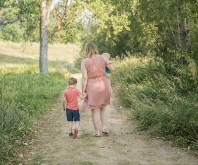 a mother walking with her two boys, one is in her arms, the other walks beside her holding her hand, they are on a dirt path walking toward the sun with green leaves and bushes surrounding them