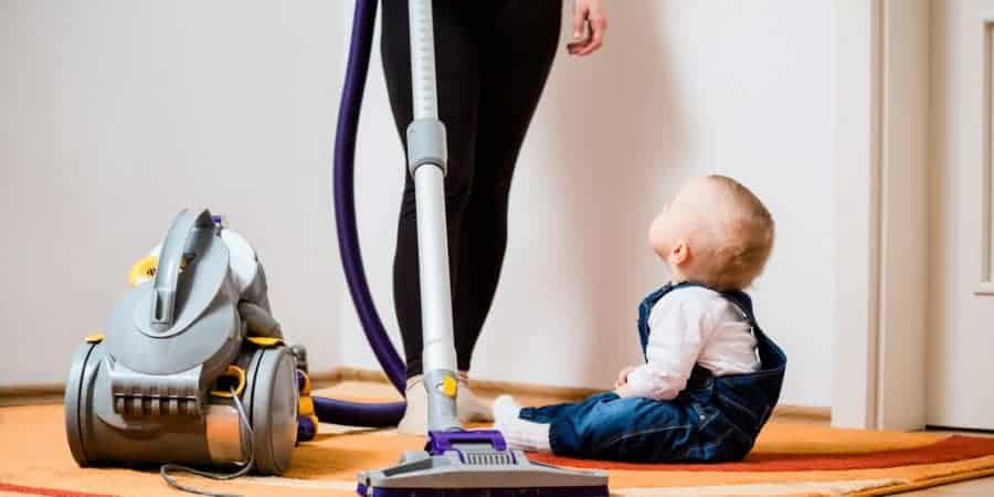 """a mother is vacuuming her floor while her baby sits on the floor and looks up at her; feature image for the blog post titled """"how to keep your house clean when you have little kids"""" by forgotten lattes"""