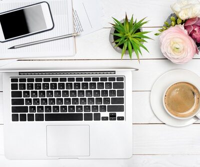 a flat lay of items on a white wood table; the times are blogger essentials and include an open silver laptop, a smart phone, a small green plant, a cup of coffee, and a pink flower for a pop of color