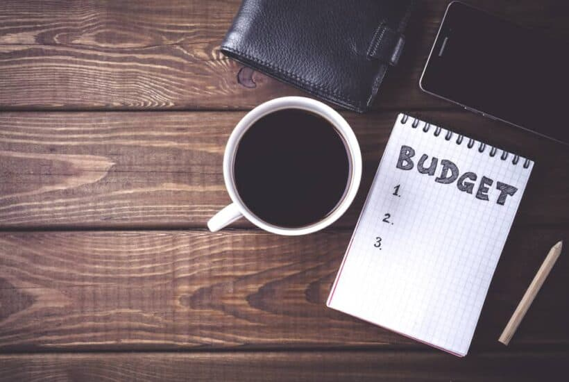 """a wood table with a cup of coffee, a notebook sits next to it with the word""""budget"""" written in bold letters; feature image for budgeting for a large family by forgotten lattes"""