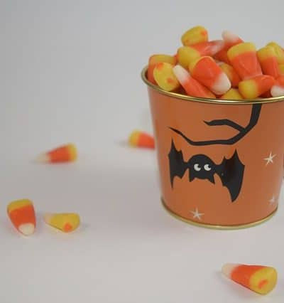 white background and a white table with a small orange bucket with a black bat on it, candy corn is overflowing from the bucket and has spilled onto the white table