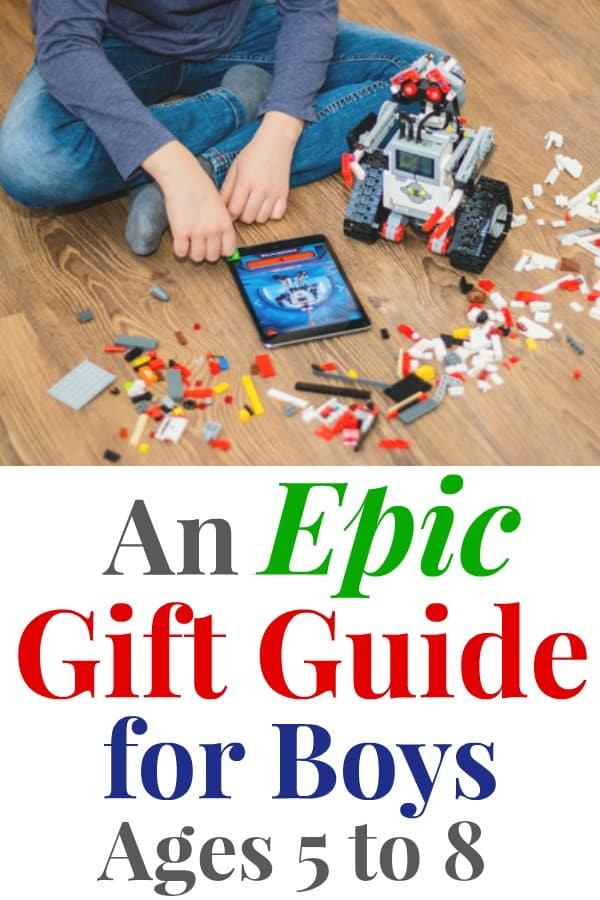 """graphic with a picture above and text below; picture is a young boy sitting on the floor surrounded by multi-colored LEGO bricks, a toy robot is beside the boy the robot is built from LEGO bricks, there is an iPad on the floor directly in front of the boy; the text below reads """"An Epic Gift Guide for Boys Ages 5 to 8"""""""
