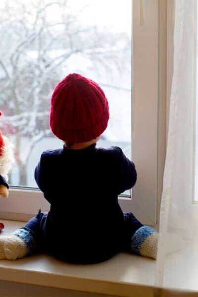 young child sitting on a windowsill next to a toy gnome watching snow fall outside the window