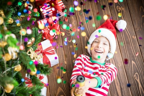 a young boy in red and white striped pajamas is laying on his back under a colorfully decorate Christmas tree, he is wearing a red Santa hat and is holding a party popper that is releasing confetti all around him