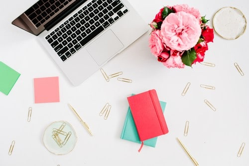 Flat lay home office desk. Female workspace with laptop, pink and red roses bouquet, golden accessories, red and mint diary on white background. Top view feminine background.