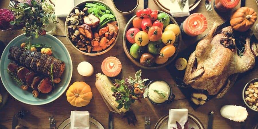 a wood table with all the fixings of an epic thanksgiving dinner including bread, vegetables, a roasted turkey, place settings, a salad, etc.