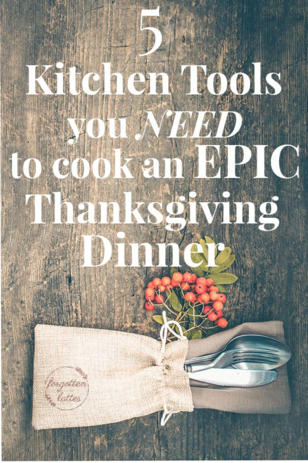 "a dark wood table with a rustic place setting, a brown burlap napkin tied with twine, silverware tucked inside the napkin, cranberries fresh on the stem; the text over the picture reads ""5 kitchen tools you need to cook an epic thanksgiving dinner"""