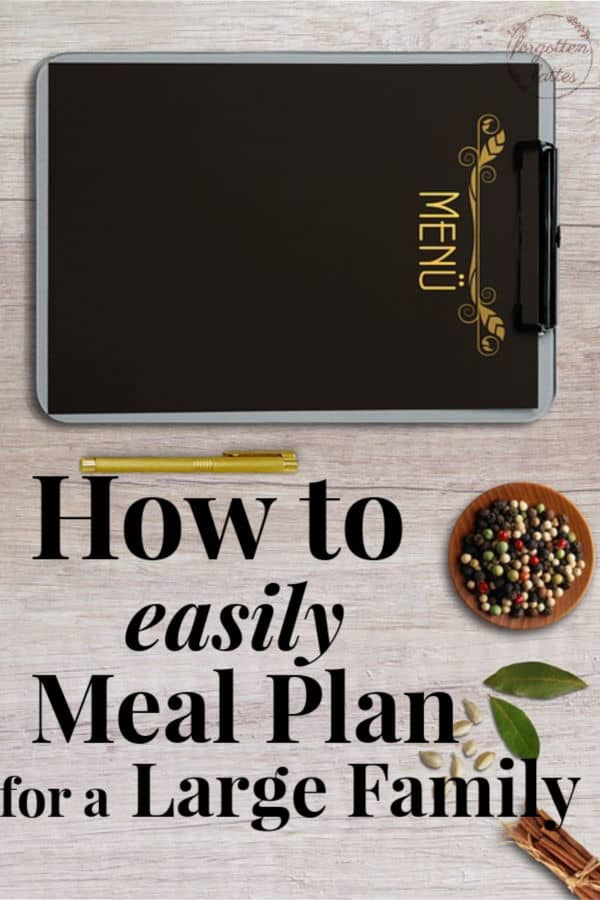 "grey distressed wood with a black board laying on top that reads ""Menu"" in yellow writing, a yellow pen sits next to the board, small bowls of spices and herbs sit in the upper right corner of the frame text overlay reads ""How to easily meal plan for a large family"""