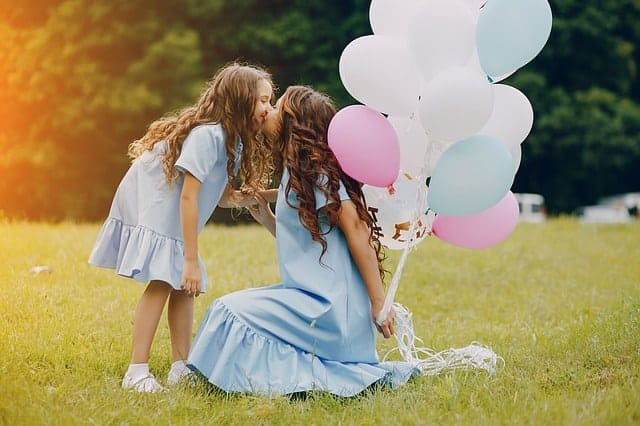 a mother and daughter are pictured, both are wearing blue dresses, the mom is kneeling down, the young daughter is bending down to kiss her mother on the lips, mom is holding blue white and pink balloons; they are outside in the grass with trees behind them; busy moms