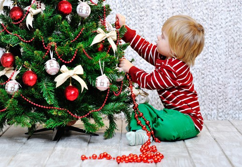 toddler boy sits on the floor next to a decorated Christmas tree; he is pulling a strand of red beads off of the tree