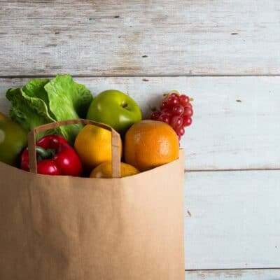 white distressed wood as a background for a large brown bag overflowing with groceries, colorful fruits and vegetable spill out of the top of the bag as it lays on the wood