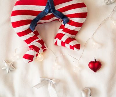 close up picture of baby feet in red and white striped pajamas with a navy blue stripe under the buttons, the baby is laying on a white blanket with red and silver christmas tree ornaments around the baby