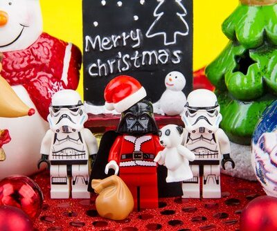 "star wars lego men wearing santa hats with a small chalkboard that says ""merry christmas"" behind them"