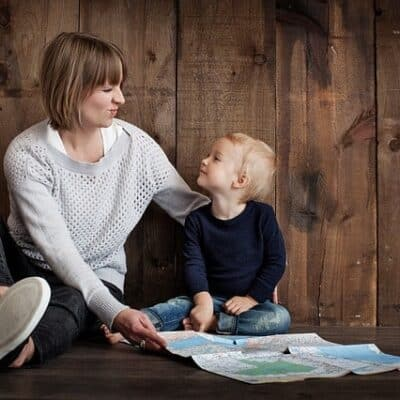 "a mother and her son sitting on the floor looking at one another, smiling; this is the feature image for an article titled ""The importance of letting your children face natural consequences"" by the parenting blog Forgotten Lattes"