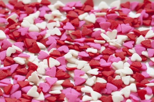 "a pile of red, pink, and white candy hearts scattered on a white background; this is the feature image for the article titled ""10 Easy Valentine's Day Ideas for Kids"" by the Motherhood blog Forgotten Lattes"