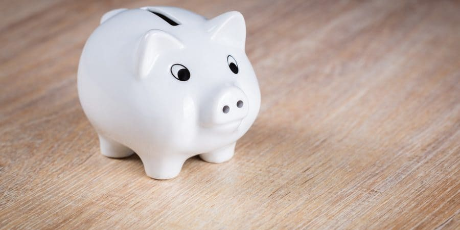 "a small white piggy bank sits on a light wood surface; this is the feature image for the article titled ""10 easy ways for your family to save money"""