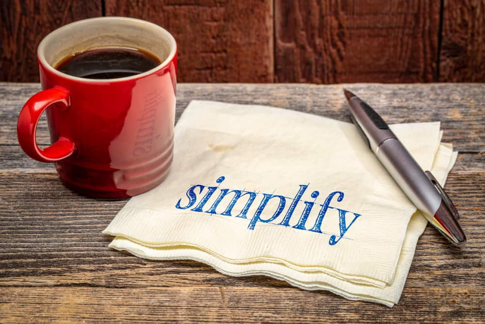 simplify advice - handwriting on a napkin with a cup of coffee against rustic wood; and image featured in the post titled how to declutter your home when you feel overwhelmed by the mom blog Forgotten Lattes
