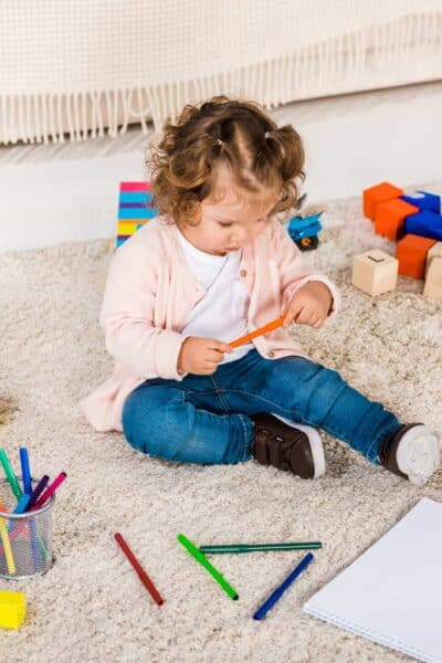 a young toddler sits on the floor surrounded by toys
