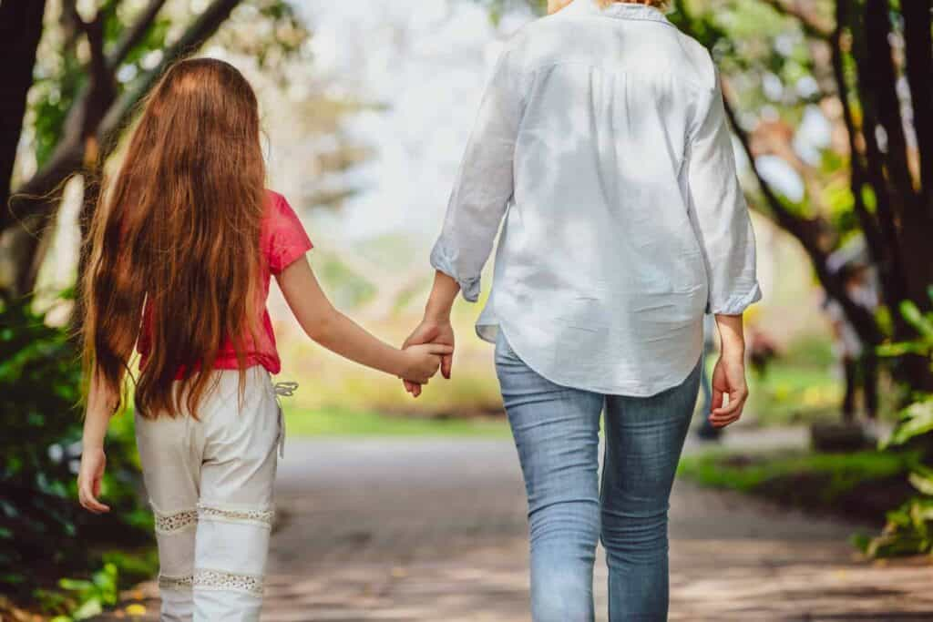 mom and daughter walk happily along a dirt path outside, mom is happy because she finally decided to stop apologizing for her daughter's normal child behavior