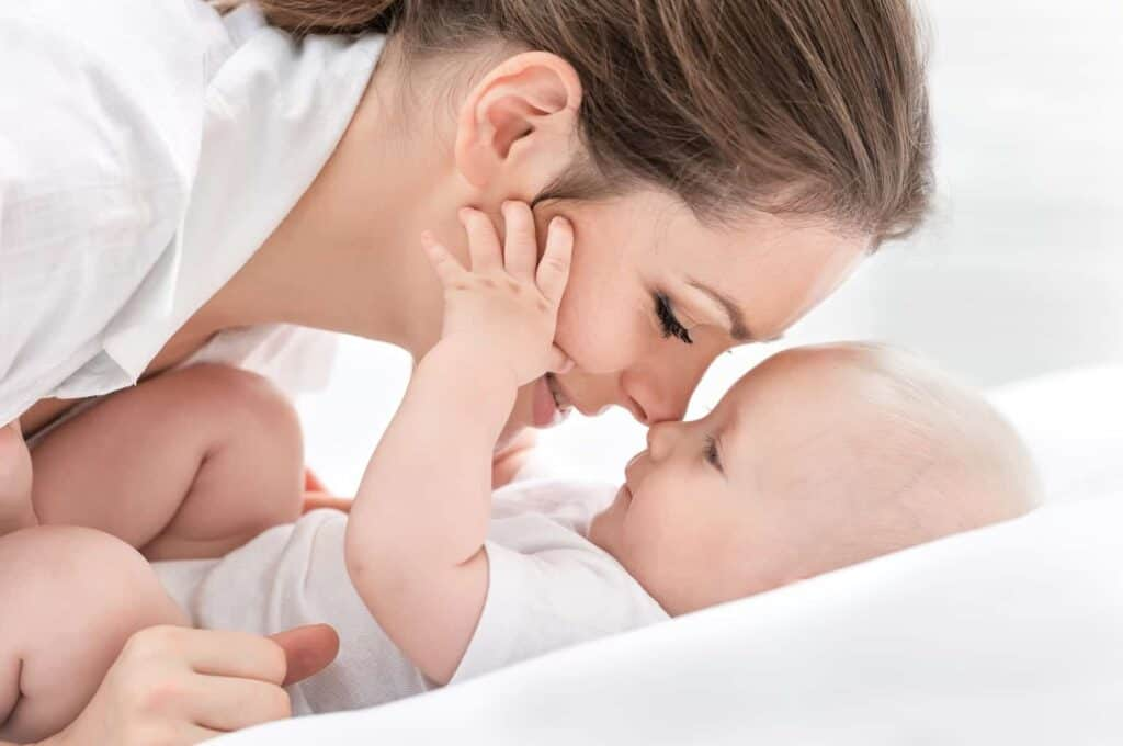 a new mom is snuggling her newborn baby, the baby is dressed in white lying on a white bed